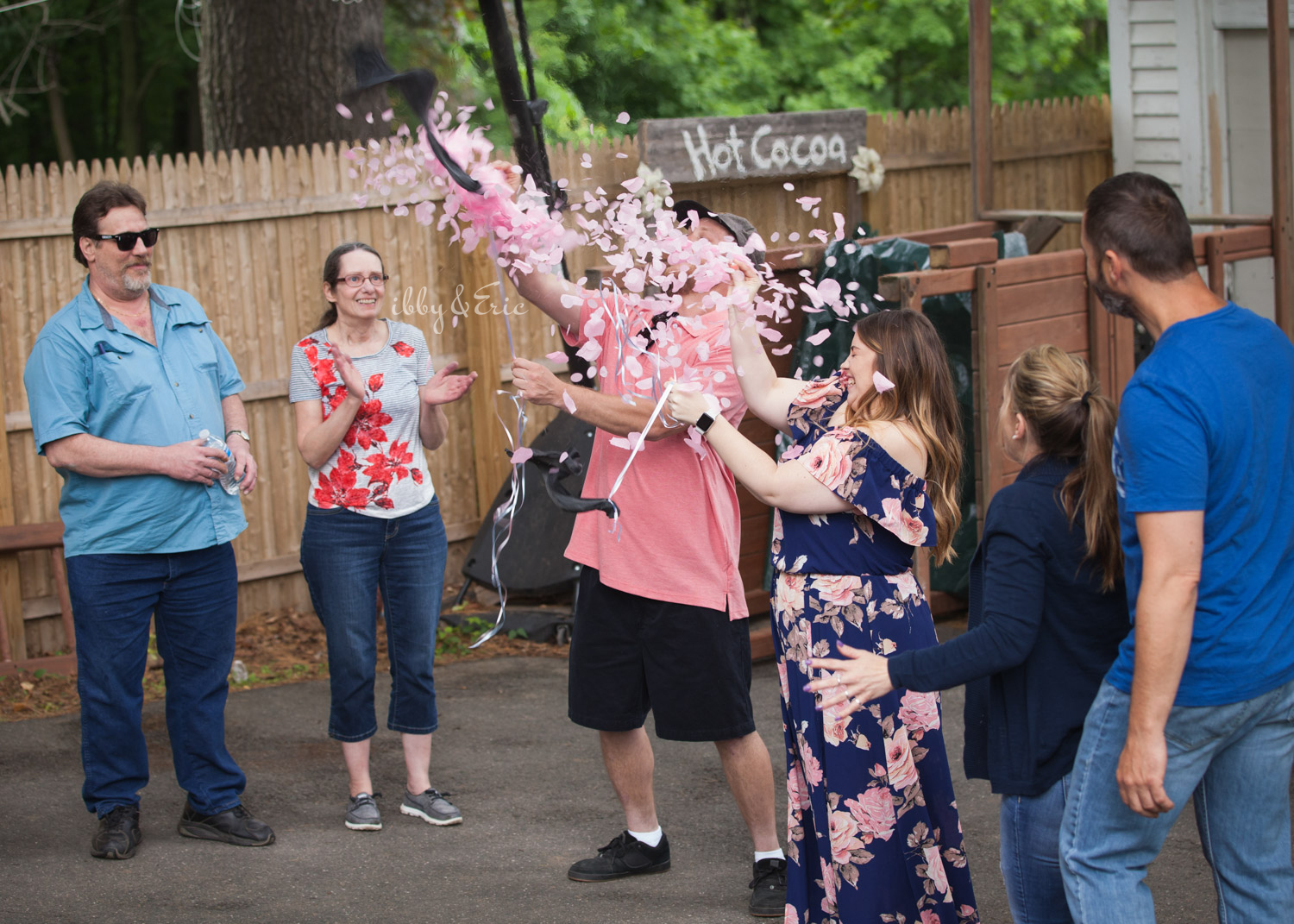 Excited parents-to-be pop a balloon to reveal pink confetti - it's a girl!