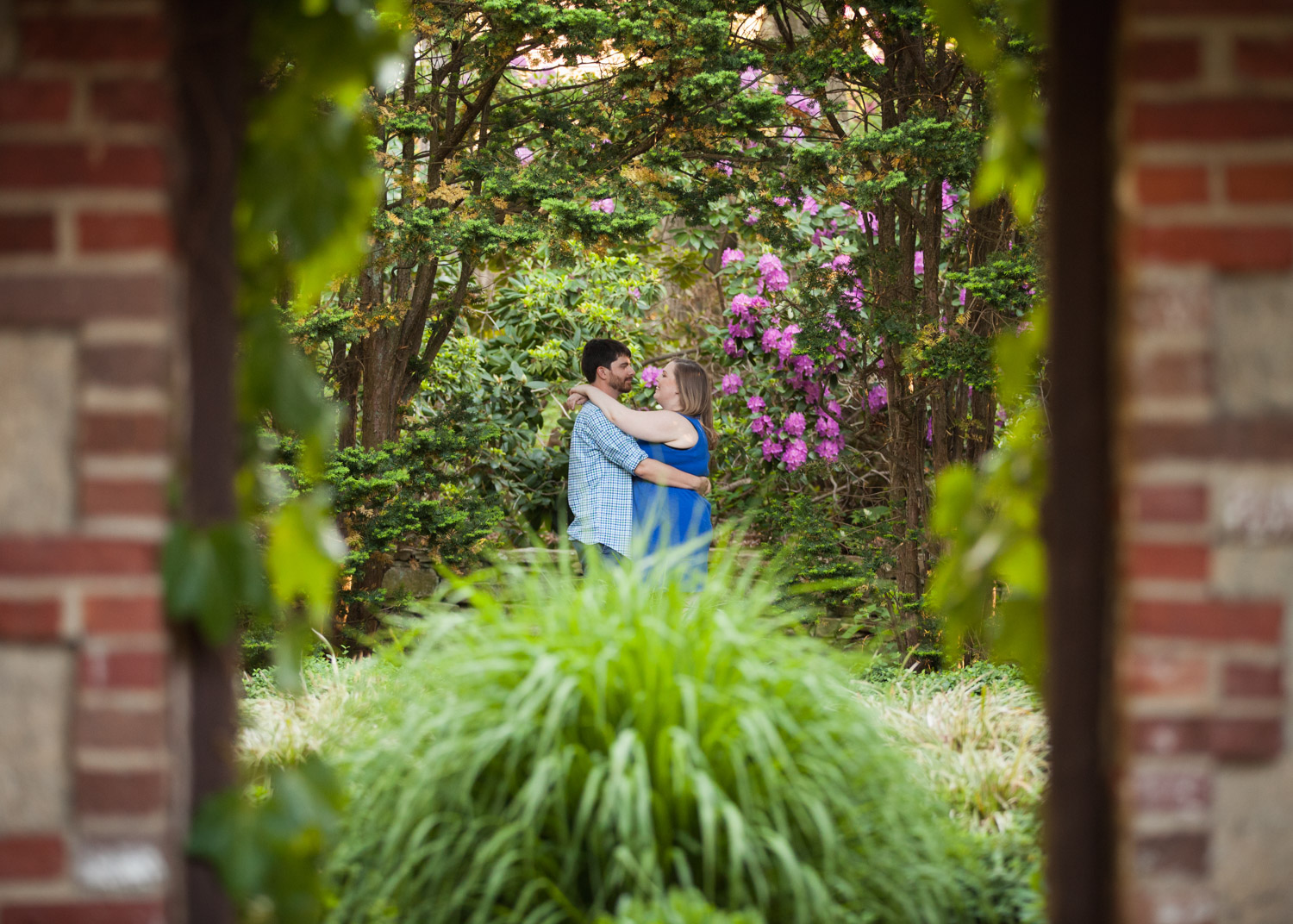 Happy couple looking at each other while hugging in the gardens at Higgins House in at WPI in Worcester, MA