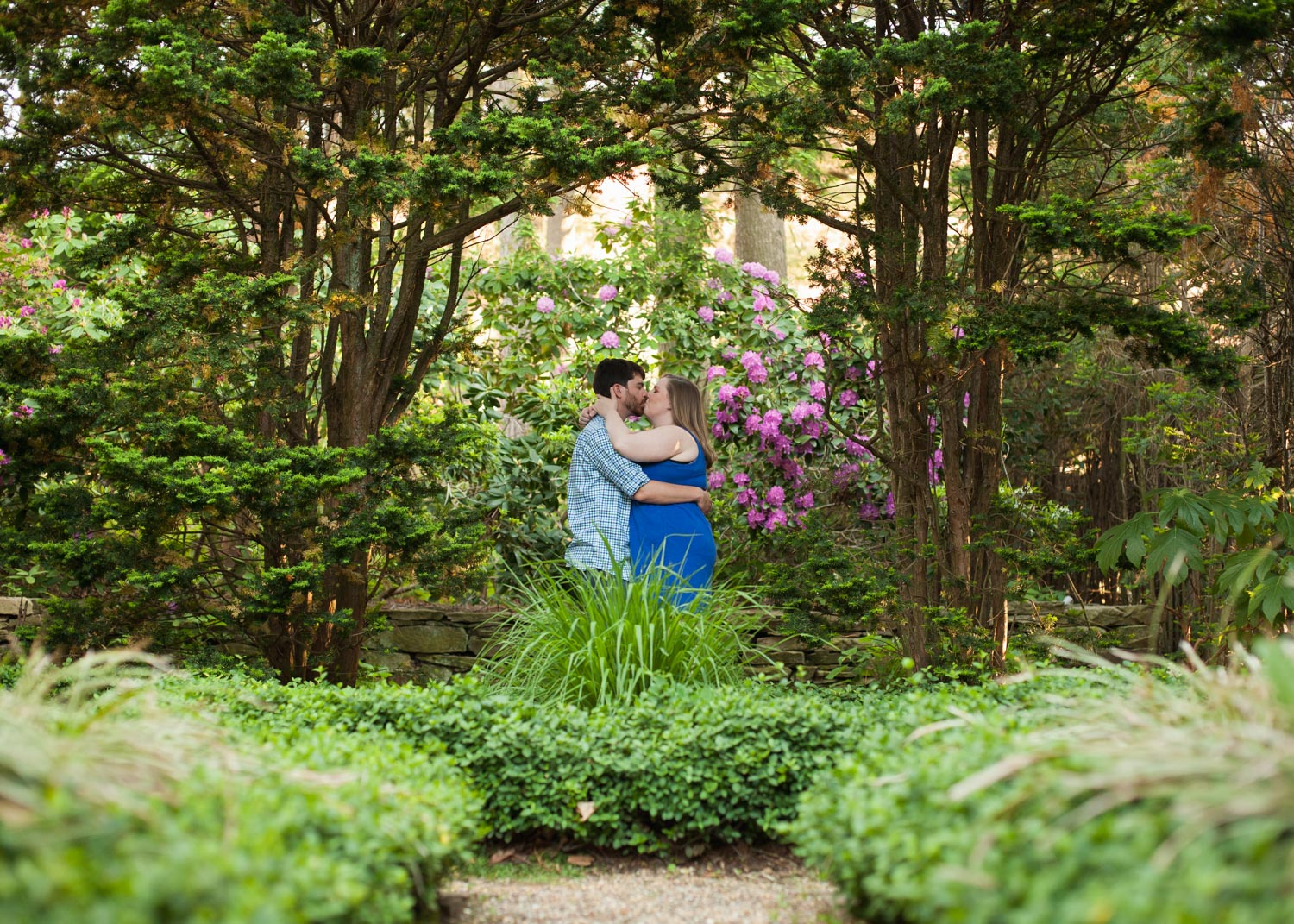 A couple wearing blue for their engagement photos kisses in the gardens of Higgins House in Worcester, MA.