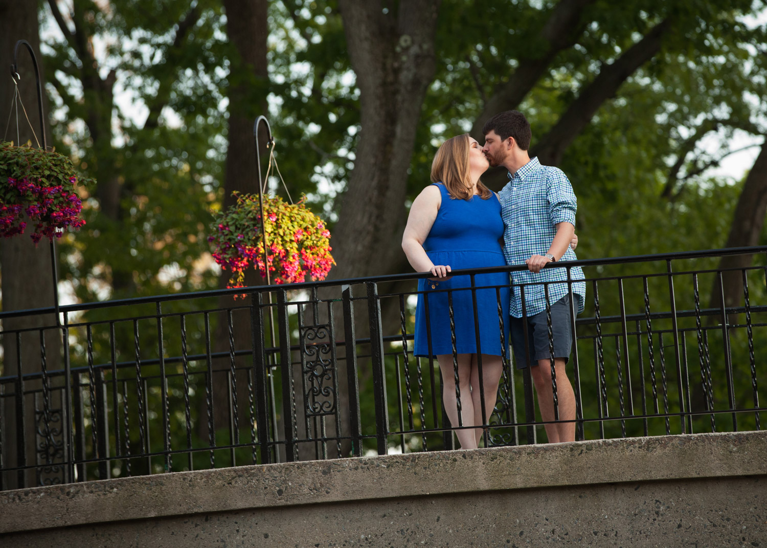 A couple wearing blue kisses on a bridge during their city engagement photos in Worcester, Massachusetts.