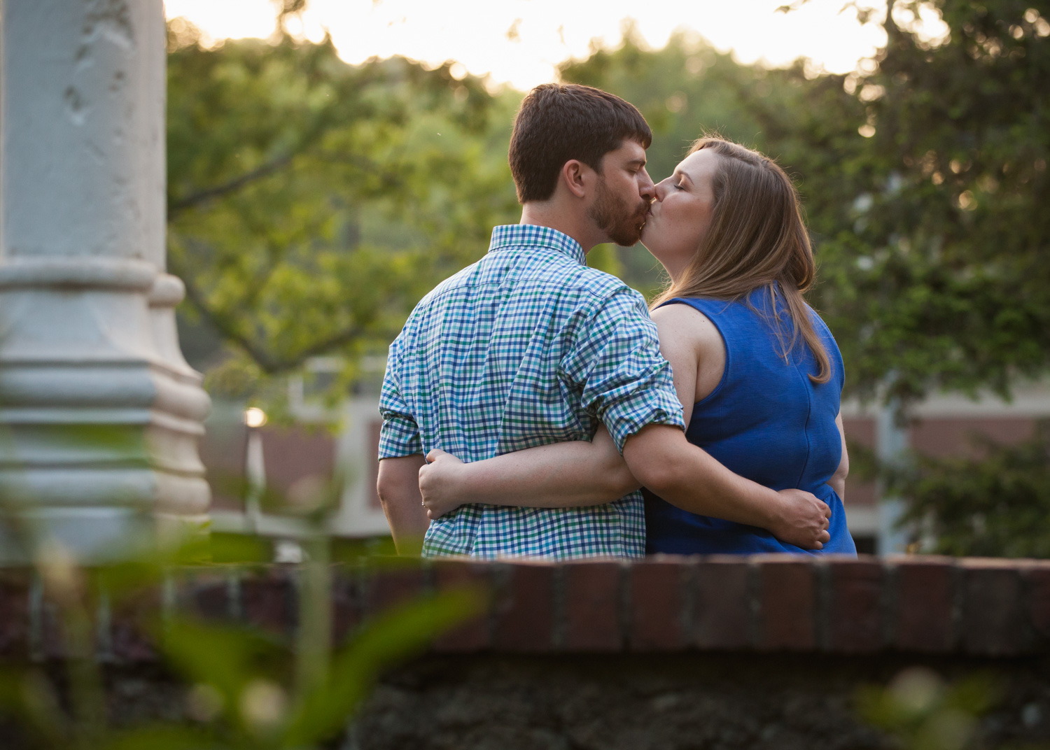 Couple kisses at sunset in the gardens of Worcester Polytechnic Institute's Higgins House in Massachusetts.