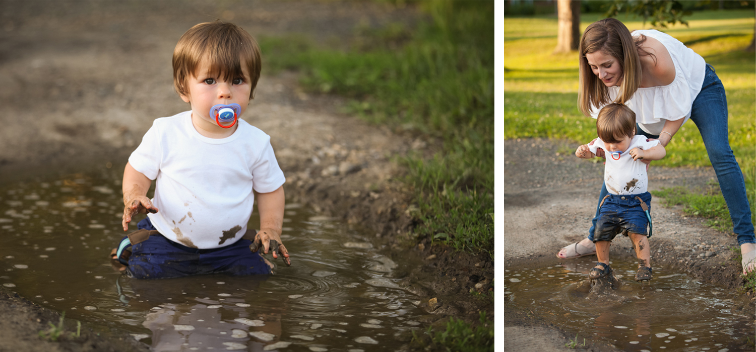 Toddler boy wearing white tee shirt sits in a mud puddle and mom picks him up.