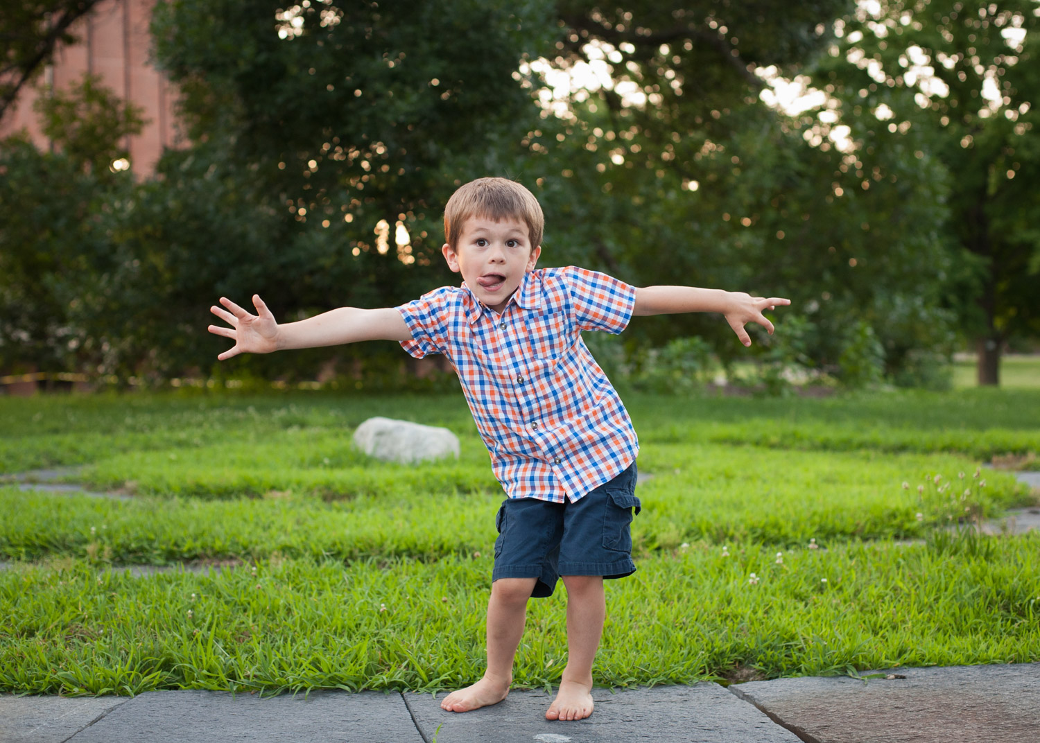 Young boy wearing orange and blue plaid shirt makes a silly face with his arms outstretched.