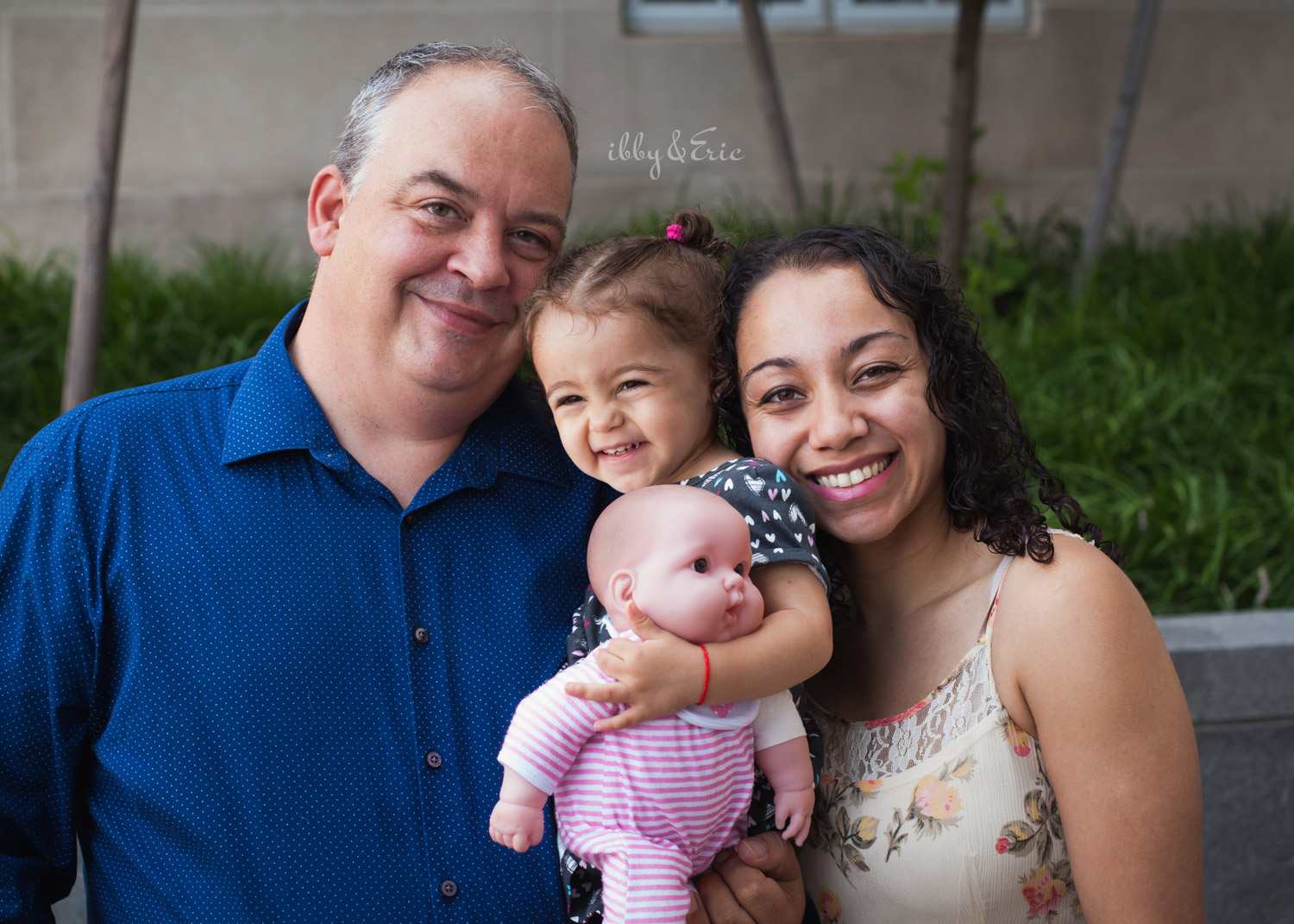 Mom, dad, and two year old daughter holding a baby doll smile together after their adoption ceremony in Greenfield, MA.