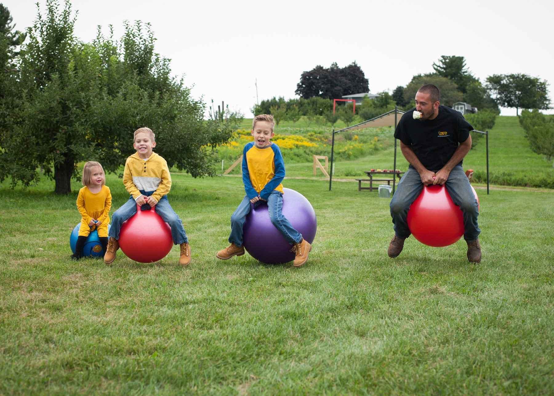 Three kids and their dad line up and race on giant bouncing balls in a field.