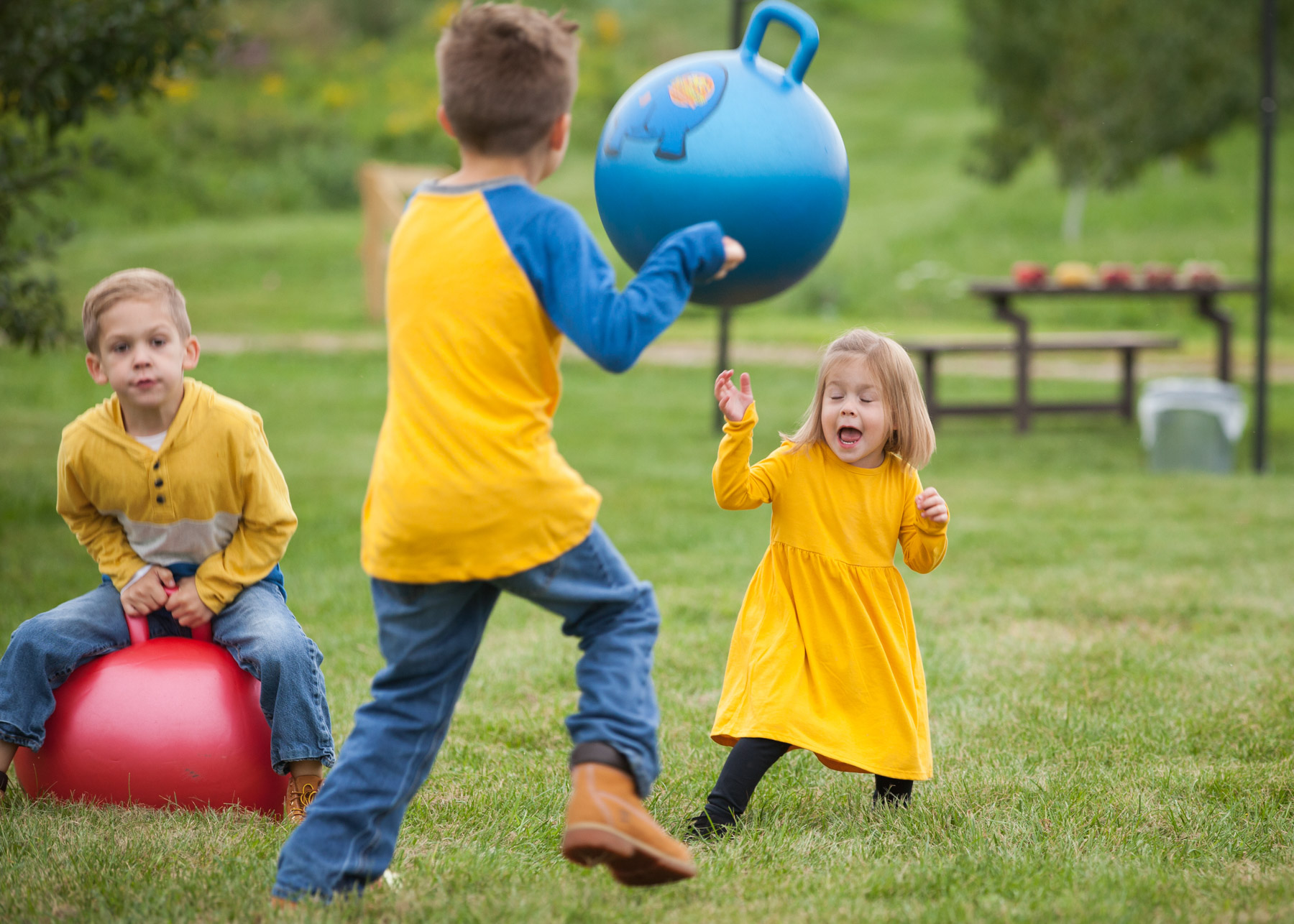Toddler girl in yellow dress makes a shocked face as she dodges the ball her is throwing at her.