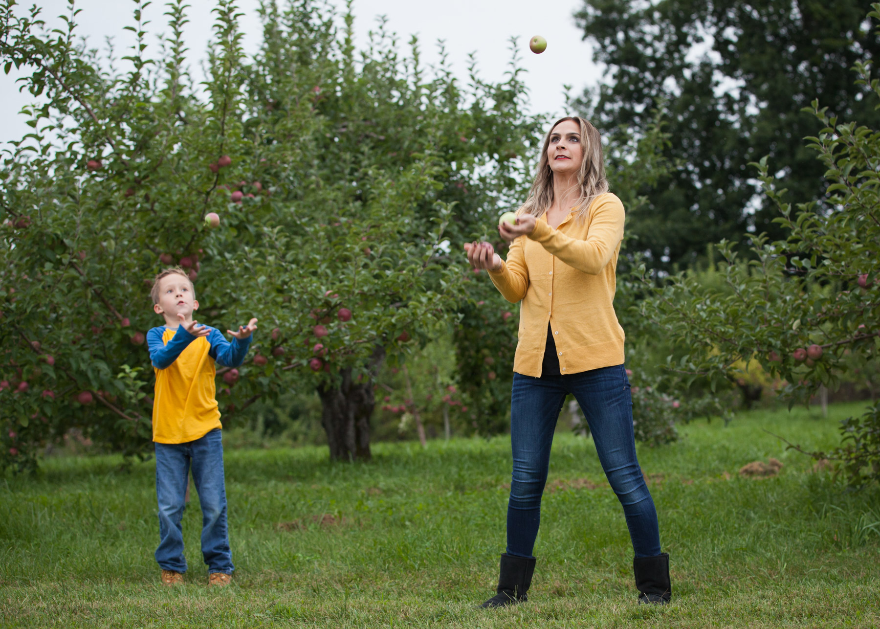 Mother and son juggle apples in an apple orchard in Easthampton, MA.