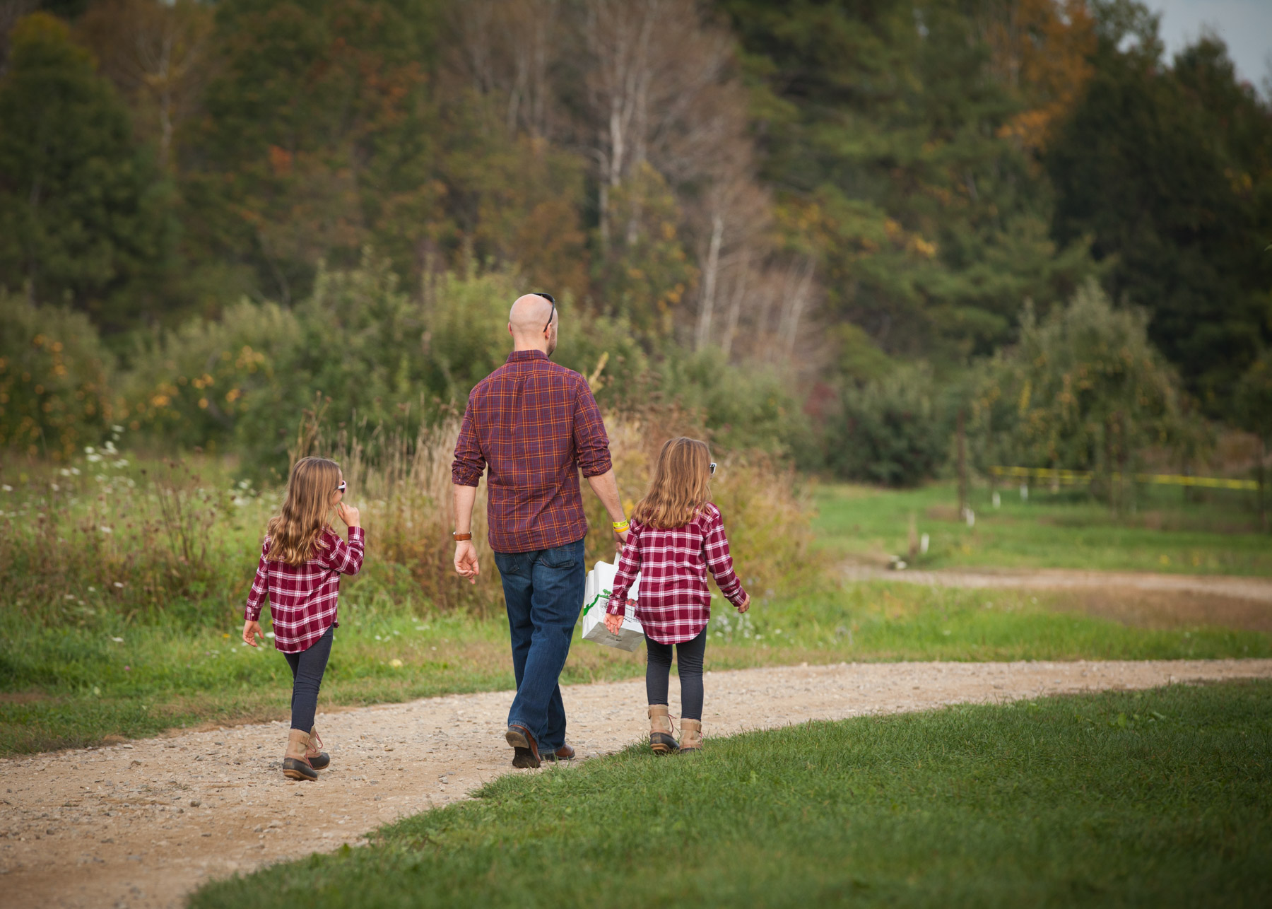 Dad and his daughters, all wearing jeans and red plaid flannel shirts, walk down a dirt path towards an apple orchard.