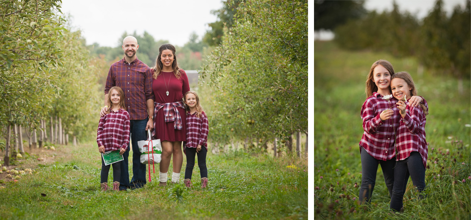 Family of four wearing burgundy plaid flannel stands together between rows of apple trees.