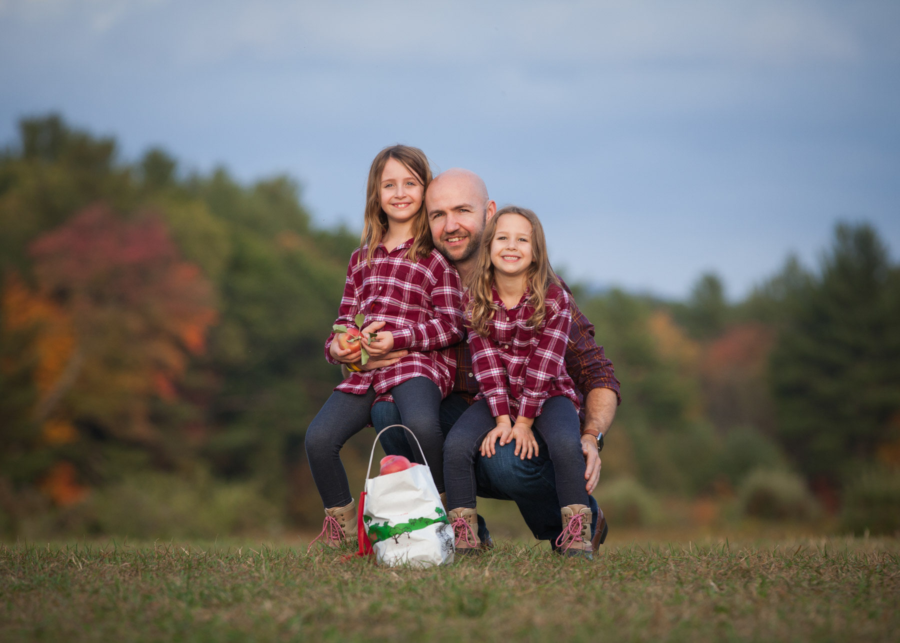 Dad and his daughters, wearing matching flannel shirts, sit together on a hill with a peck of apples in front and fall foliage behind them.