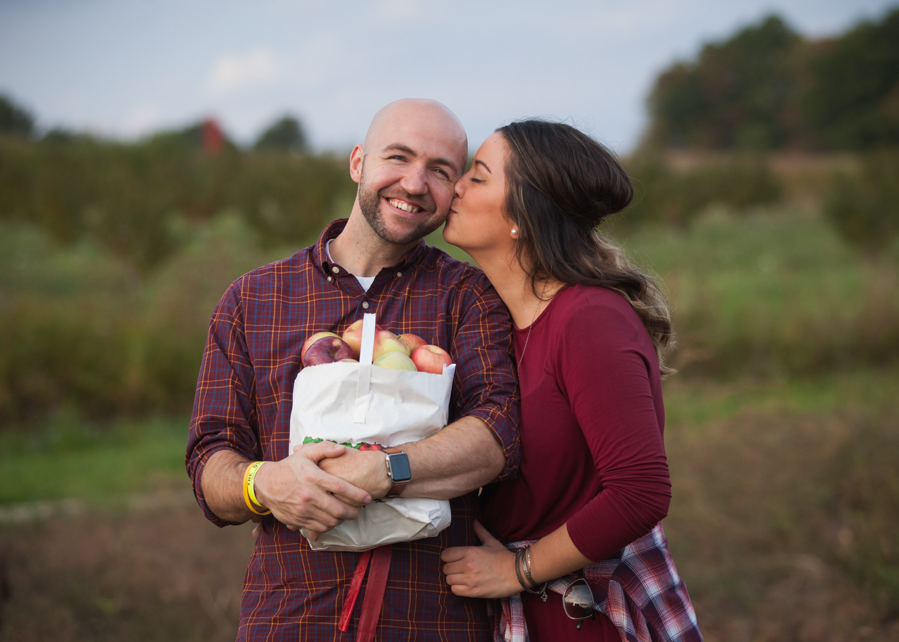 Woman with dark hair, wearing a burgundy shirt, kisses her boyfriend on the cheek while he smiles and holds a bag of apples.