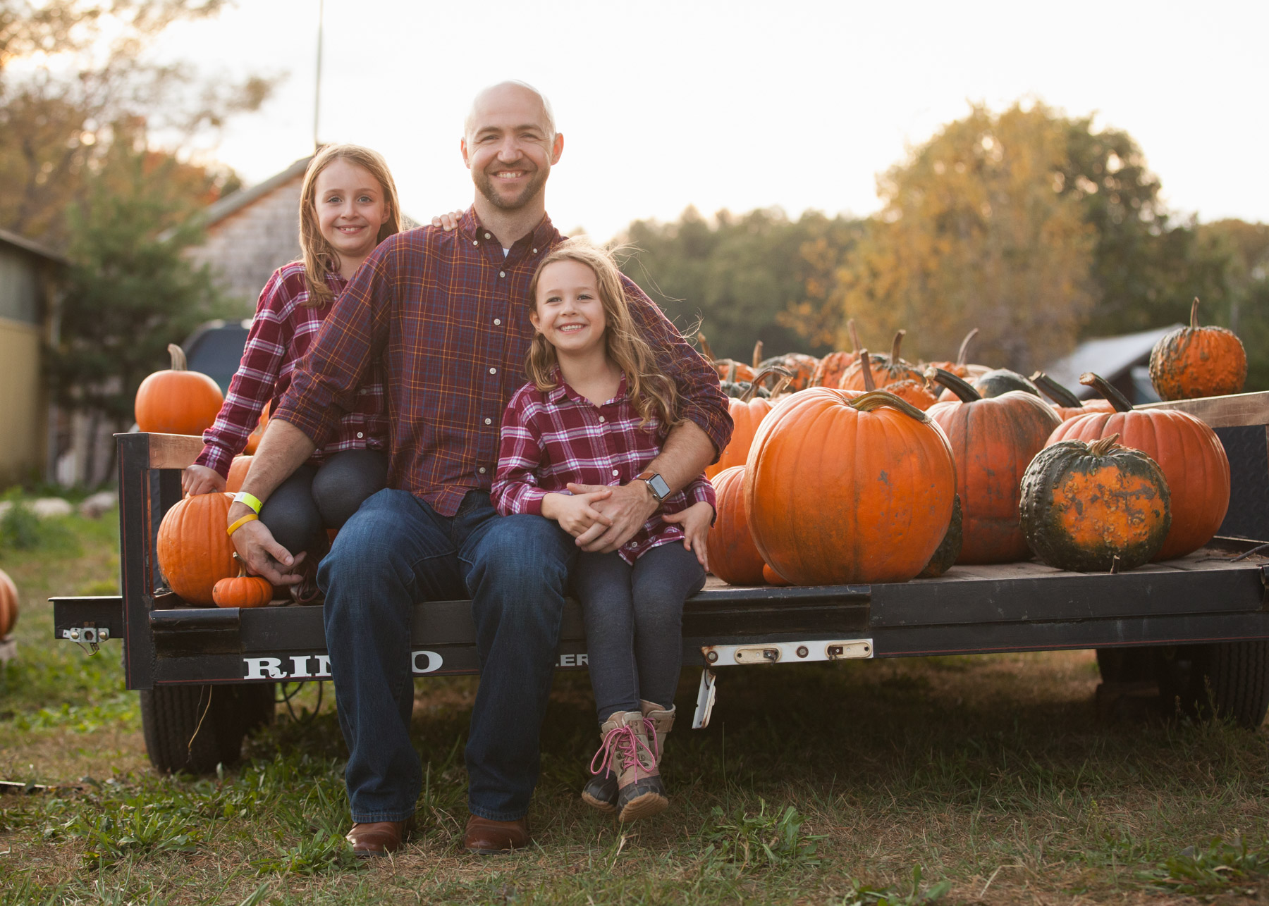 Dad and his two daughters sit on the back of a farm trailer filled with pumpkins just before sunset.
