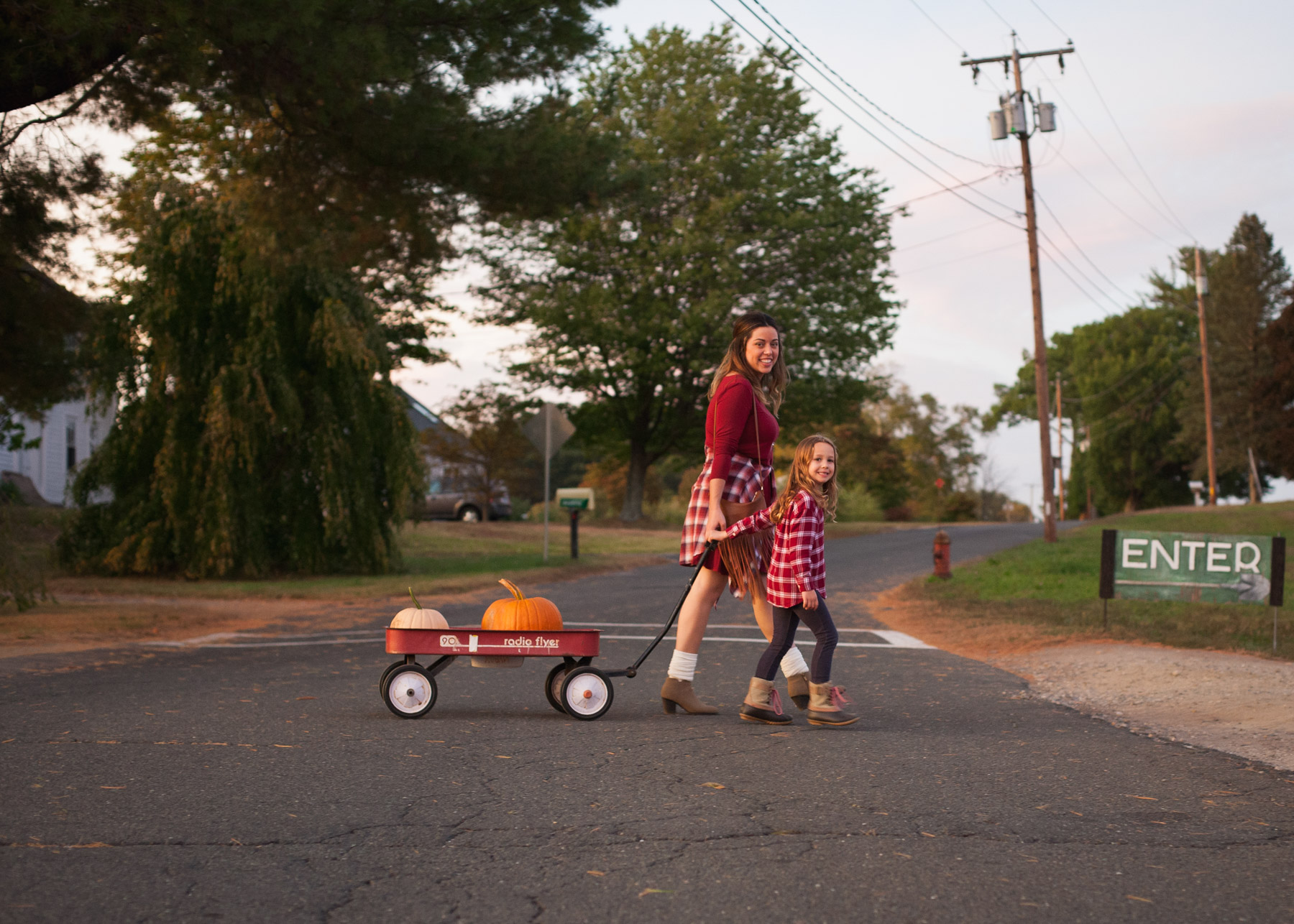 Woman and young girl, wearing matching burgundy and plaid outfits, cross the street pulling their pumpkins in a red radio flyer wagon.