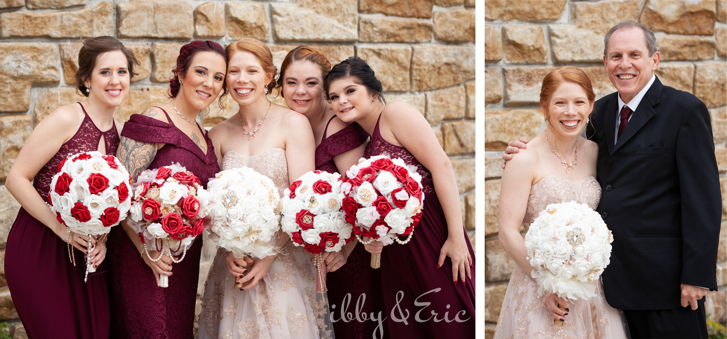 Bride with red hair poses for photos with her dad and her bridesmaids holding red and white bouquets and wearing burgundy dresses.