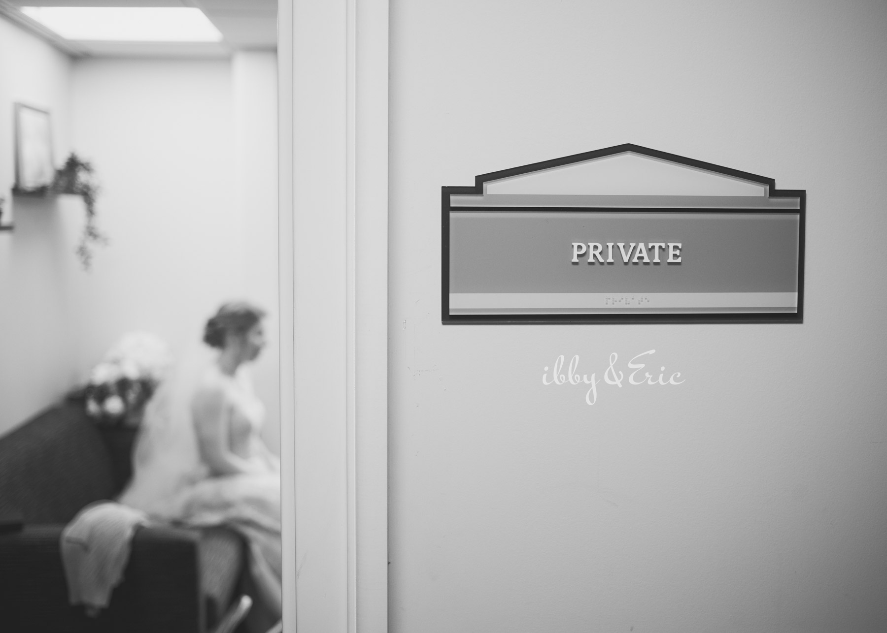 Black and white photo, focused on the PRIVATE sign on the doorway, with the bride seated in the background out of focus.
