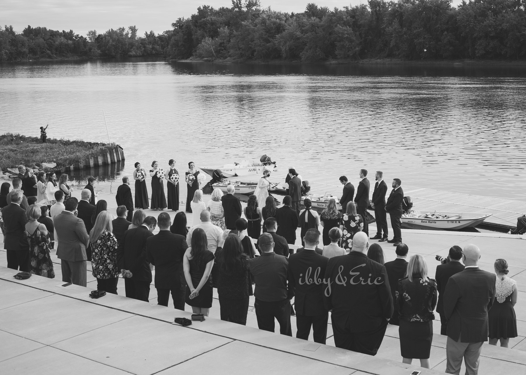 Black and white wide angle photo showing a riverfront wedding ceremony at the Glastonbury Boathouse in Connecticut.
