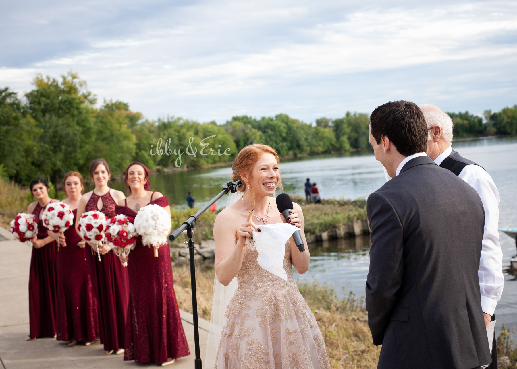 Bride smiles and laughs as she reads her wedding vows to her groom during their ceremony on the Connecticut River.