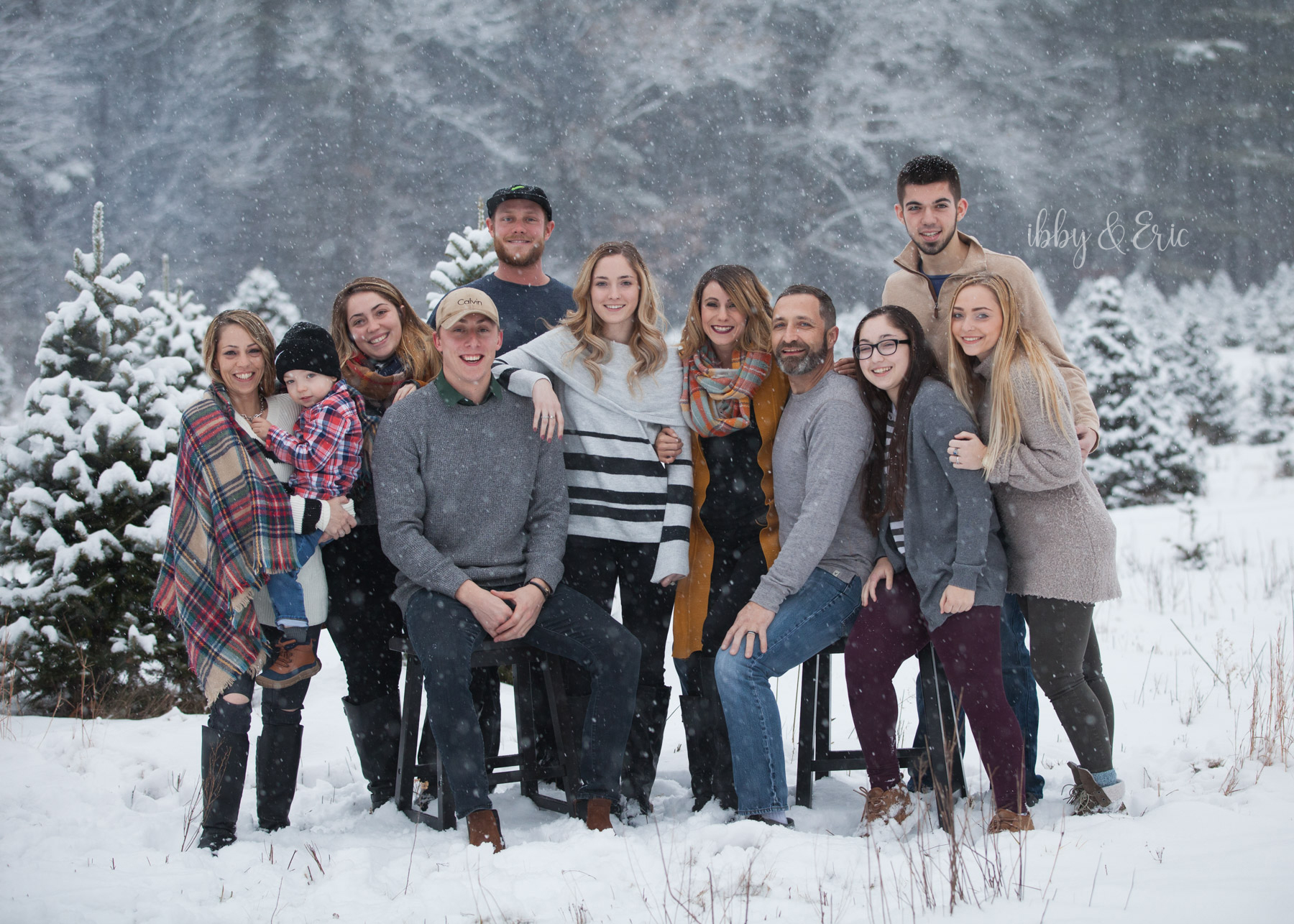 Family of 11 wearing grey and beige pose together at a Westfield, MA Christmas tree farm in a snowstorm.
