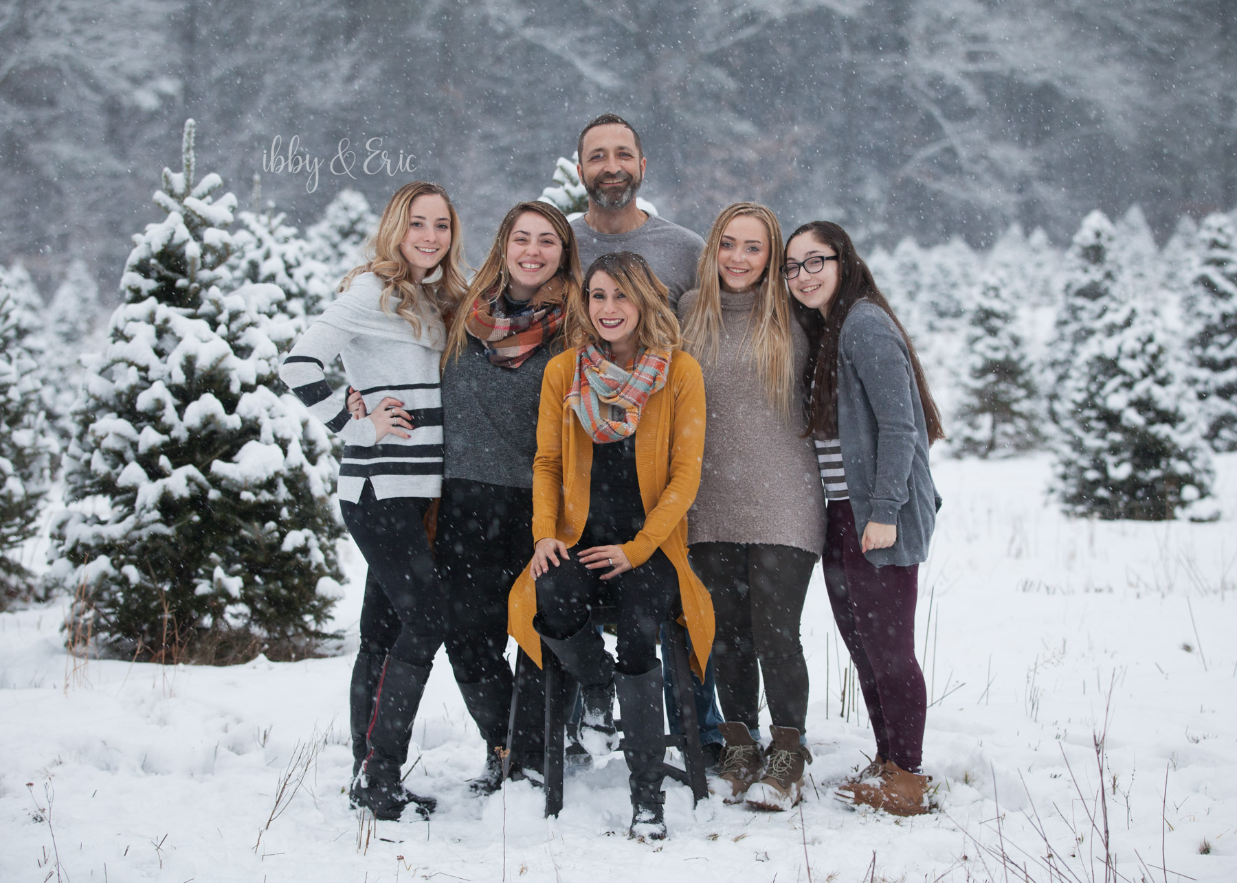 4 girls hug their dad & surround their step mom wearing mustard yellow during a snowstorm in western Massachusetts.