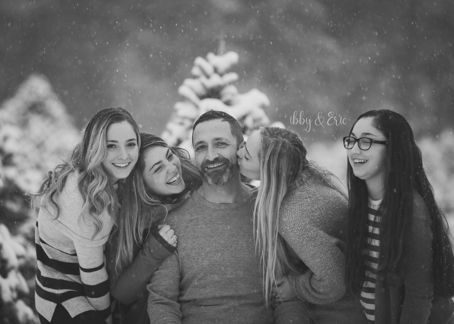 Black and white photo of four adult daughters kissing their dad on the cheek in the snow.