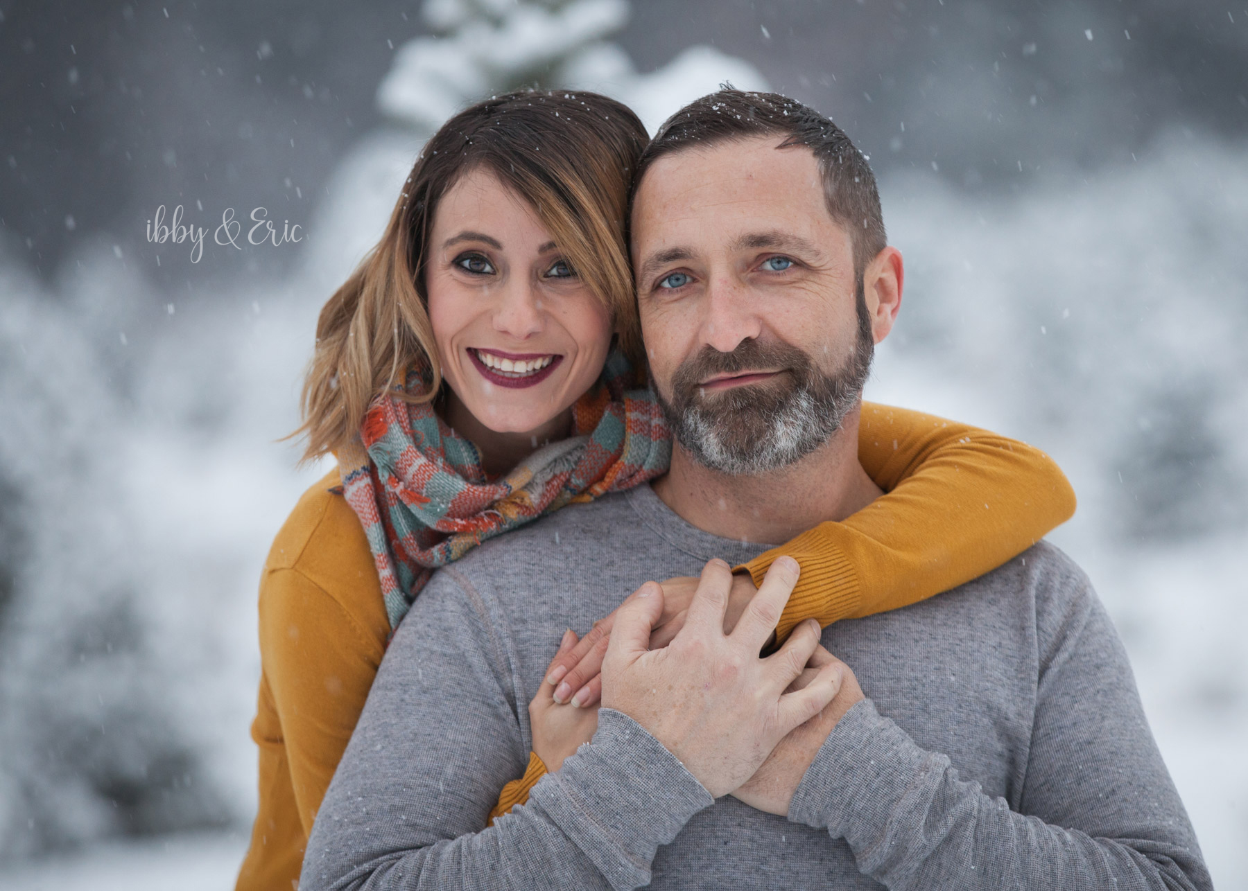 Husband & wife hug and smile in a snowstorm during their winter family pictures in Westfield, MA.