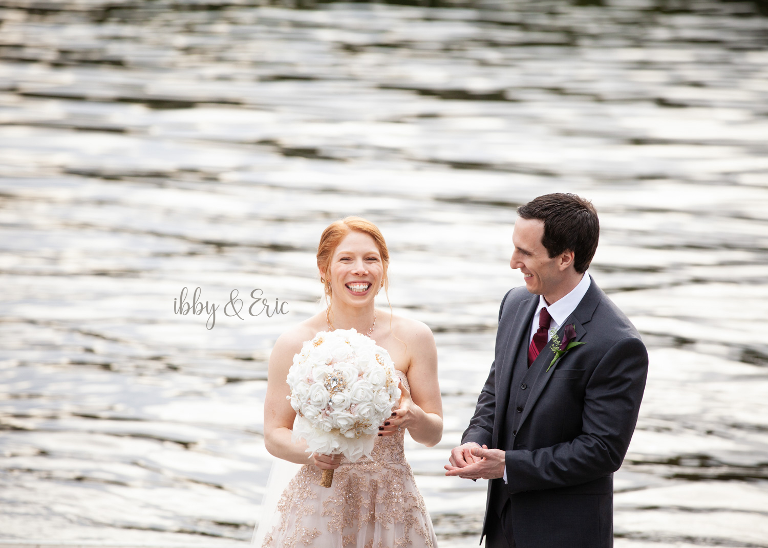 Bride and groom laugh and smile to each other while standing in front of the Connecticut River.