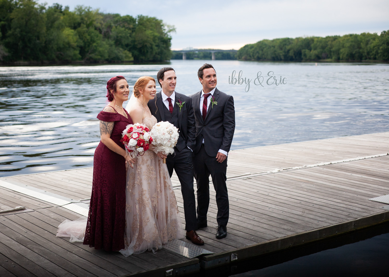 Maid of Honor, Bride, Groom and Best Man stand together on a dock and smile.