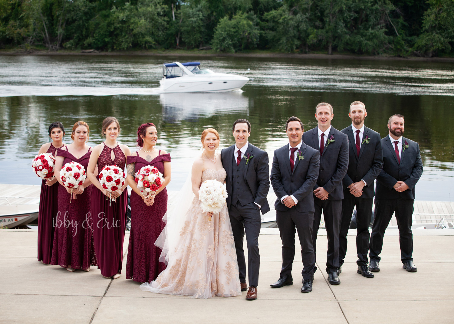 Wedding party line up with a boat driving down the river in the background.