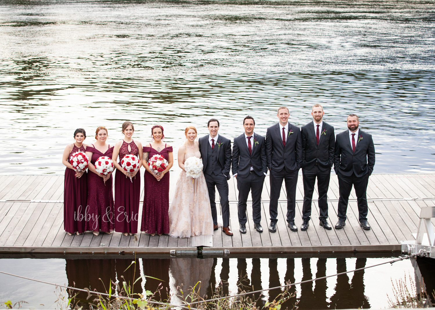 Wedding party, wearing burgundy & dark gray, lineup on a dock by the Connecticut River.