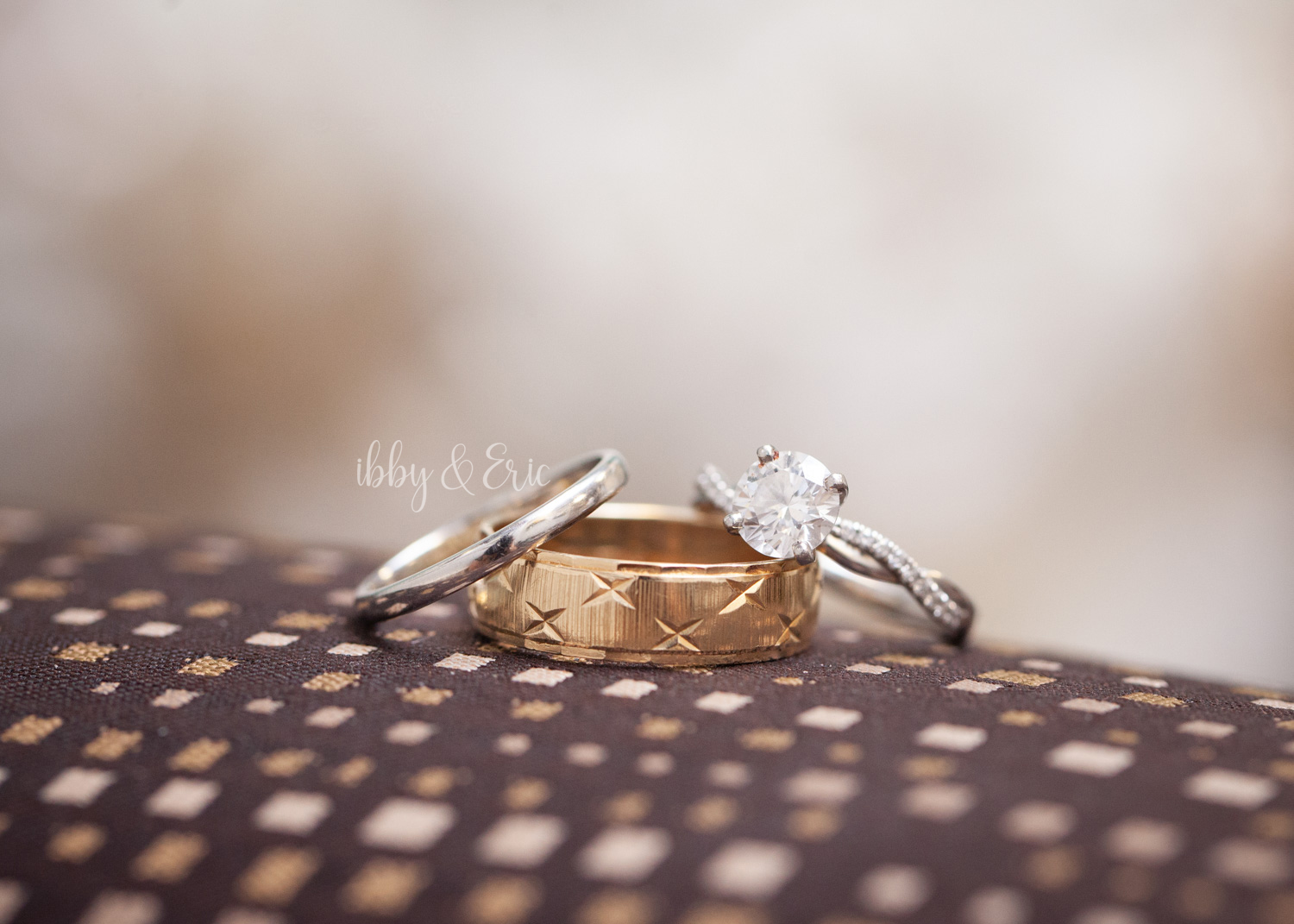 Macro, detail shot of the diamond engagement ring and wedding bands.