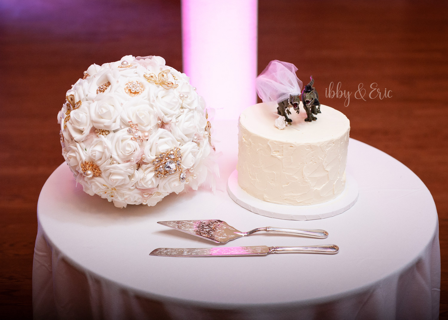 Dessert table arrangement, wedding cake with dinosaur toppers, brooch bouquet, and decorative cake servers.