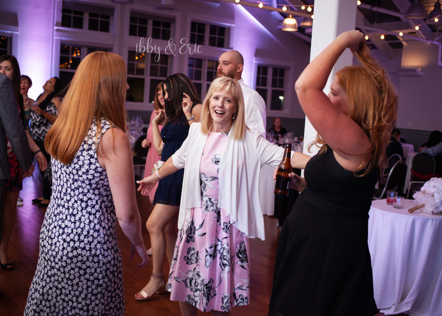 Mother of the groom wearing a pink floral dress & white sweater dances during the reception.