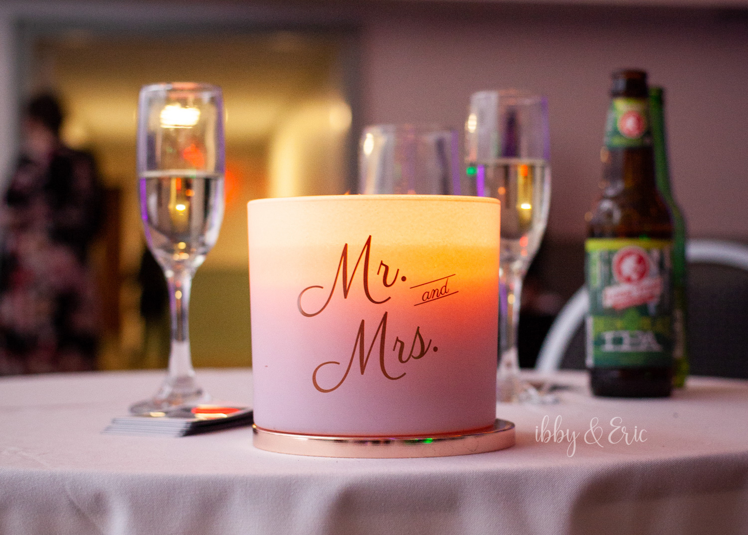 Mr. & Mrs. themed candle burns on the sweetheart table at the end of the wedding night.
