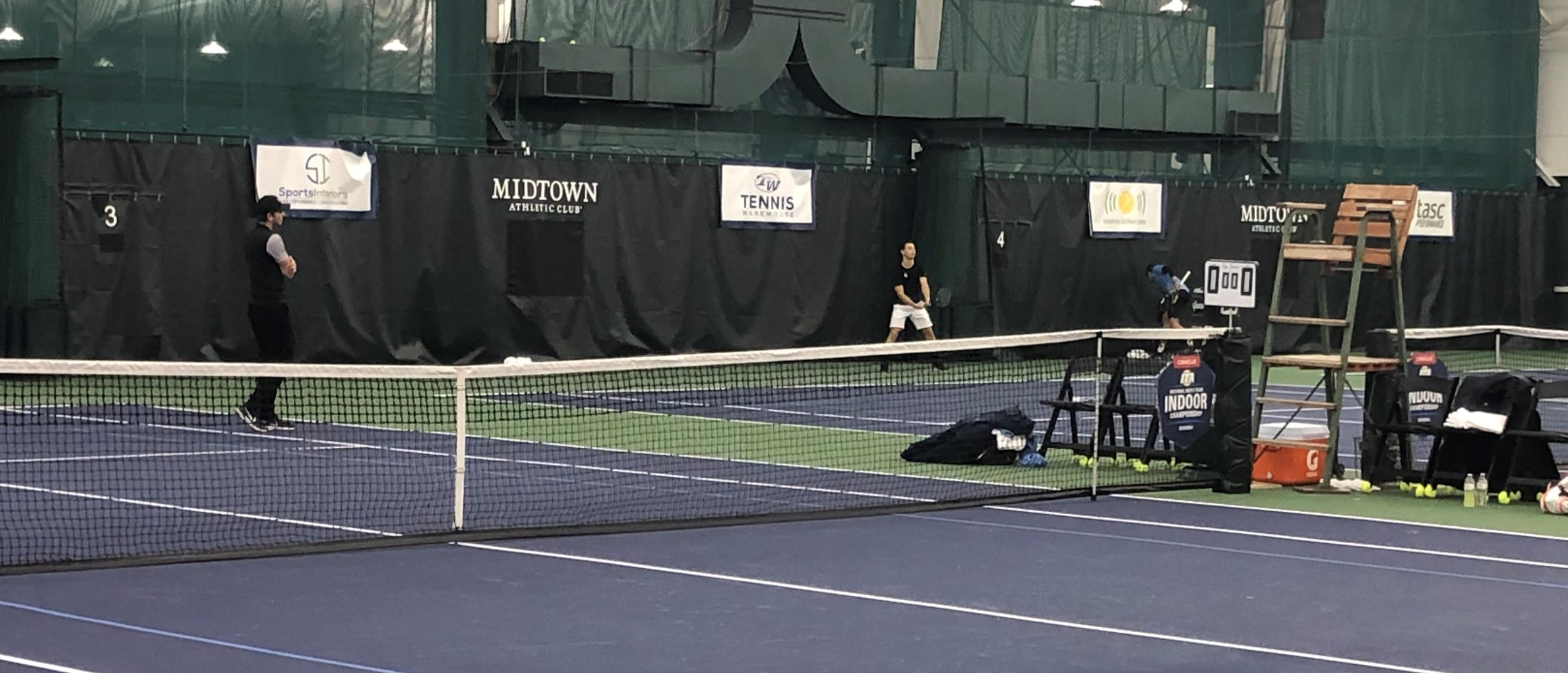 Action at the ITA National Men's Team Indoor Championship with Sports Interiors banner