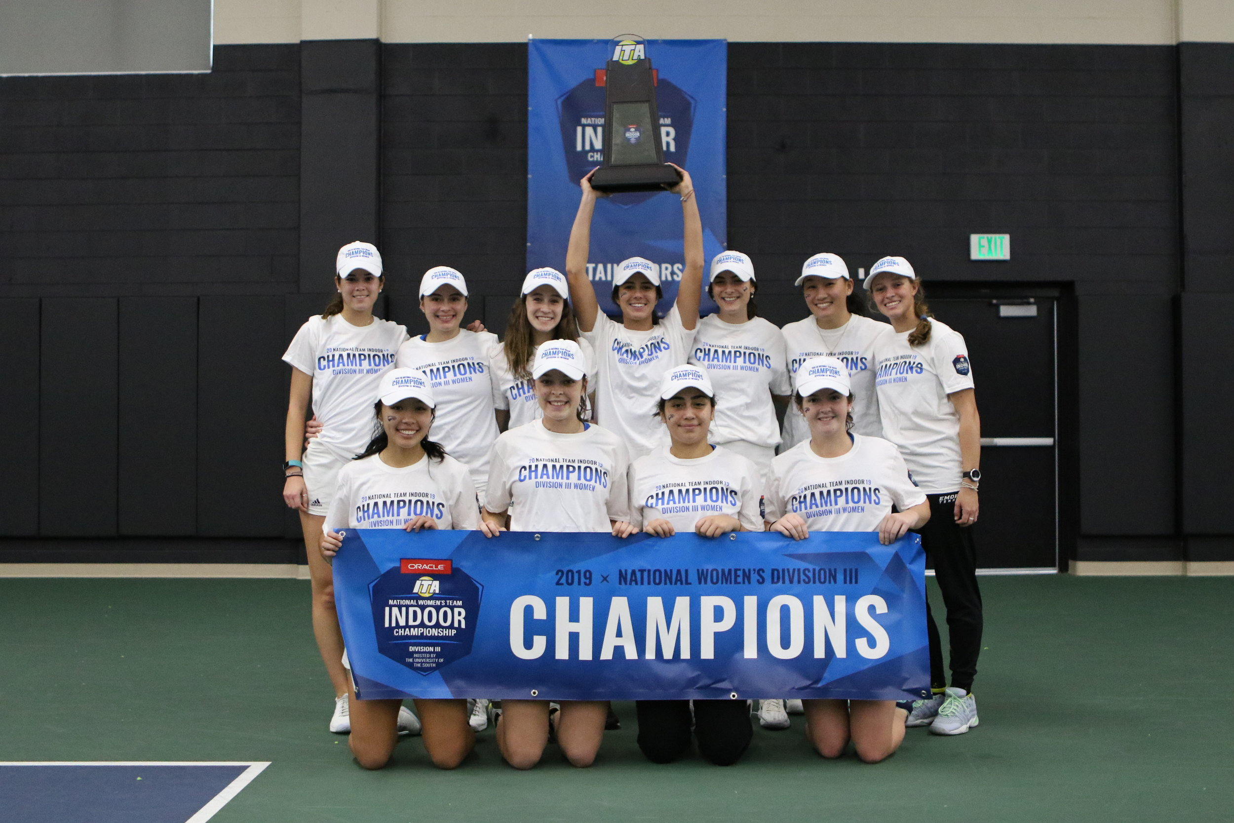 """The Emory University Women's Tennis Team beat Claremont-Mudd-Scripts College at the conclusion of the ITA Indoor Championship season this past weekend. The best 8 of the women's division III programs met in Nashville, Tennessee to compete for the crown and there was no surprise on seeding with Claremont-Mudd-Scripts holding the top spot and Emory a close second behind.  Both teams cruised to the finals with dominating team victories and the 1-vs-2 matchup was set in what was a repeat of the NCAA Final from 2018.The defending indoor champion Emory Eagles took an early lead on the one-seed Athenas with a win on court three during doubles play. Going into the singles Emory led 2-1, but that was soon equalized following a dominating performance on court 5 by CMS player Caroline Cox who won 6-3, 6-1. Emory quickly took back and extended the lead with wins on courts two and six. Eagles sophomore Defne Olcay swept Nicole Tan with identical 6-4 set wins. On six, Jessica Fatemi and Sarah Bahsoun went the distance in the first set with Fatemi outlasting Bahsoun to win 7-6. Fatemi got on a roll in the second set, though, and won 6-3 to bring Emory within match-point of claiming its third-straight indoor crown.  The top-seeded CMS refused to go away without a fight, and Rebecca Berger worked a three-set win on three to keep the Athenas' championship dreams alive. Berger traded 6-1 wins with Emory frosh Lauren Yoon before grinding out a 7-6 third-set win to make the score 4-3 with two courts active. The winning point would come from a freshman on court four, though, as Emma Cartledge swept past another freshman in Sydney Lee 7-6, 6-4 to clinch Emory's third-consecutive indoor title. (Include second photo here of the team all celebrating on the court). """"We lost to CMS in the NCAA Championship last year, so it feels good to get this win today,"""" Coach Amy Bryant of Emory University said. We know we have a long season ahead of us, and I think this provides a lot of motivation for us"""