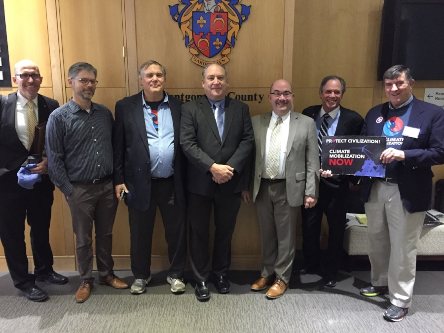 From the right, gathering outside the Montgomery County (MD) Council Meeting room are Jim Driscoll, Coordinator, MOCO Chapter of The Climate Mobilizaton (TCM), outgoing Council President Roger Berliner, Councilmembers George Leventhal and Marc Elrich, TCM Fellow Kevin Flatt, Jeff Weisner, President of the 350MOCO Steering Committee, Councilmember Tom Hucker.