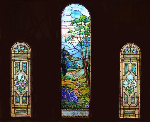 "The Stained Glass Windows in the Parish Hall - Mr and Mrs Richard F. Overbagh in 1922 donated three windows in the parish hall in memory of their late son, John C. Overbagh. At some later point this beautiful triptych in the L.C. Tiffany style became familiar to the parish as ""The Tiffany Window."" In June 2019, with the help of the Town Historian, the windows are re-attributed to Rudolph Geissler  of  Lederle and Geissler,  New York City. Louis Lederle had worked with L.C. Tiffany before joining with  Geissler around 1915.Photo credit: Neil Ralley at Stained Glass Photography"