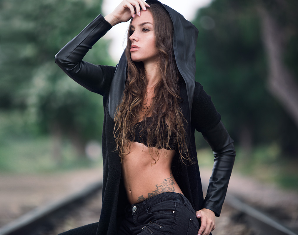 Model posing outdoors on train tracks in a crop top.