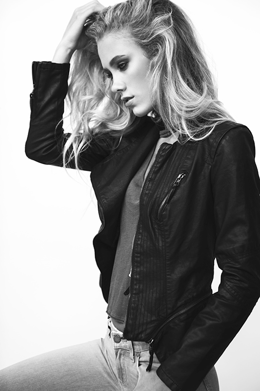Black and white photo of a model posing with black jacket.