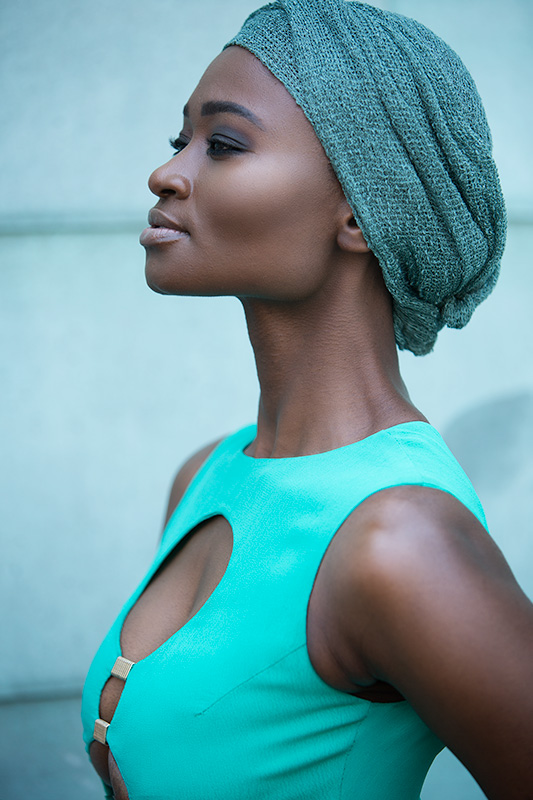 Portrait photography of a model in a turquoise dress and head piece.