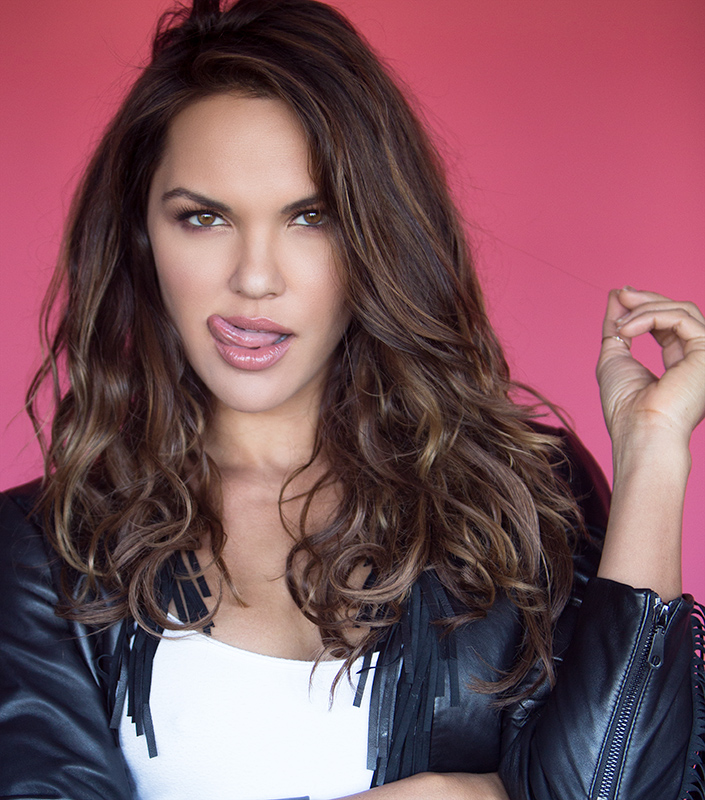 Professional model in a black leather jacket in front of a pink backdrop sticking her tongue out.