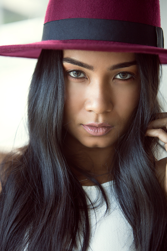 Portrait photography of a model wearing a maroon hat.