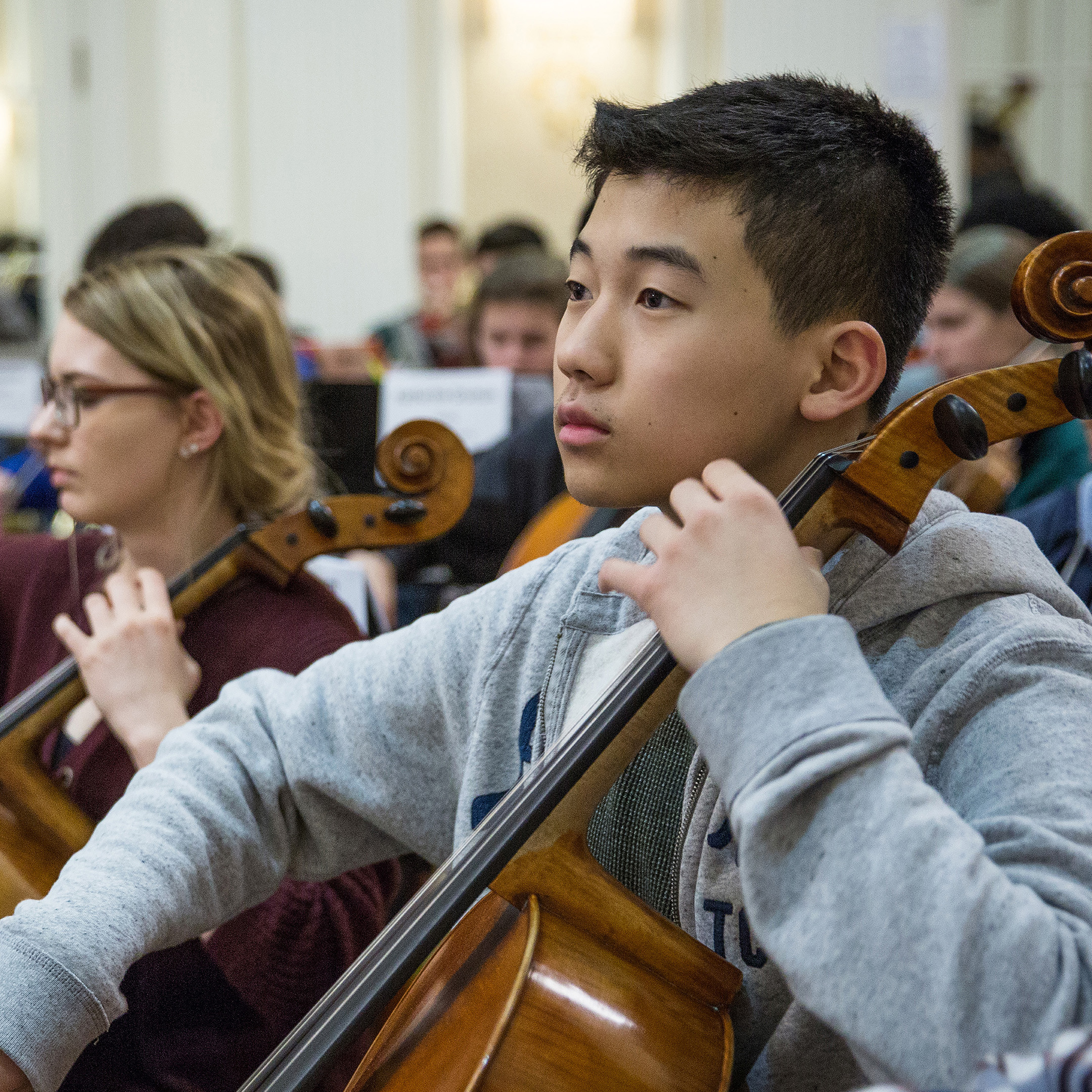 Male cello student in All-State Orchestra Rehearsal; click through to Orchestra Division Page