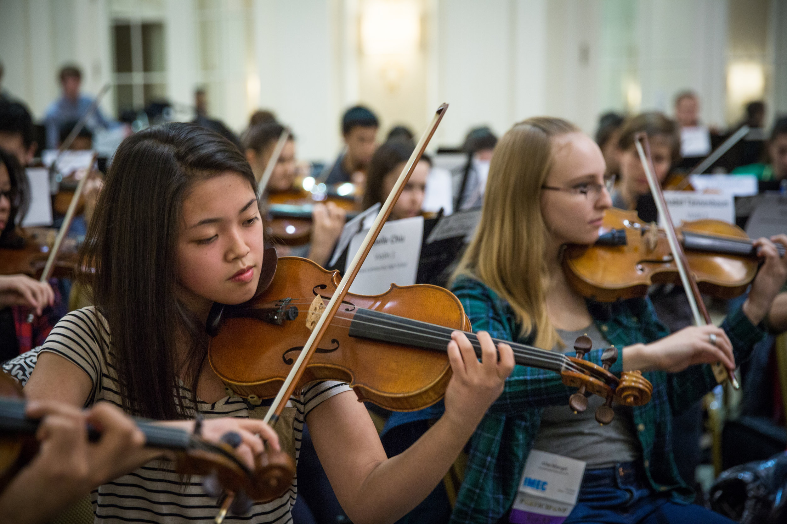 Two student violinists in the All-State Orchestra rehearsal; click through to Orchestra Audition Procedures