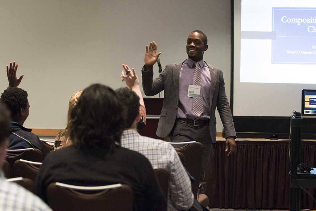 Clinician presenting to a crowd with raised hands at the Illinois Music Education Conference. No click through.