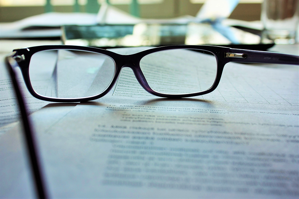 A pair of glasses sitting on pages of printed text.