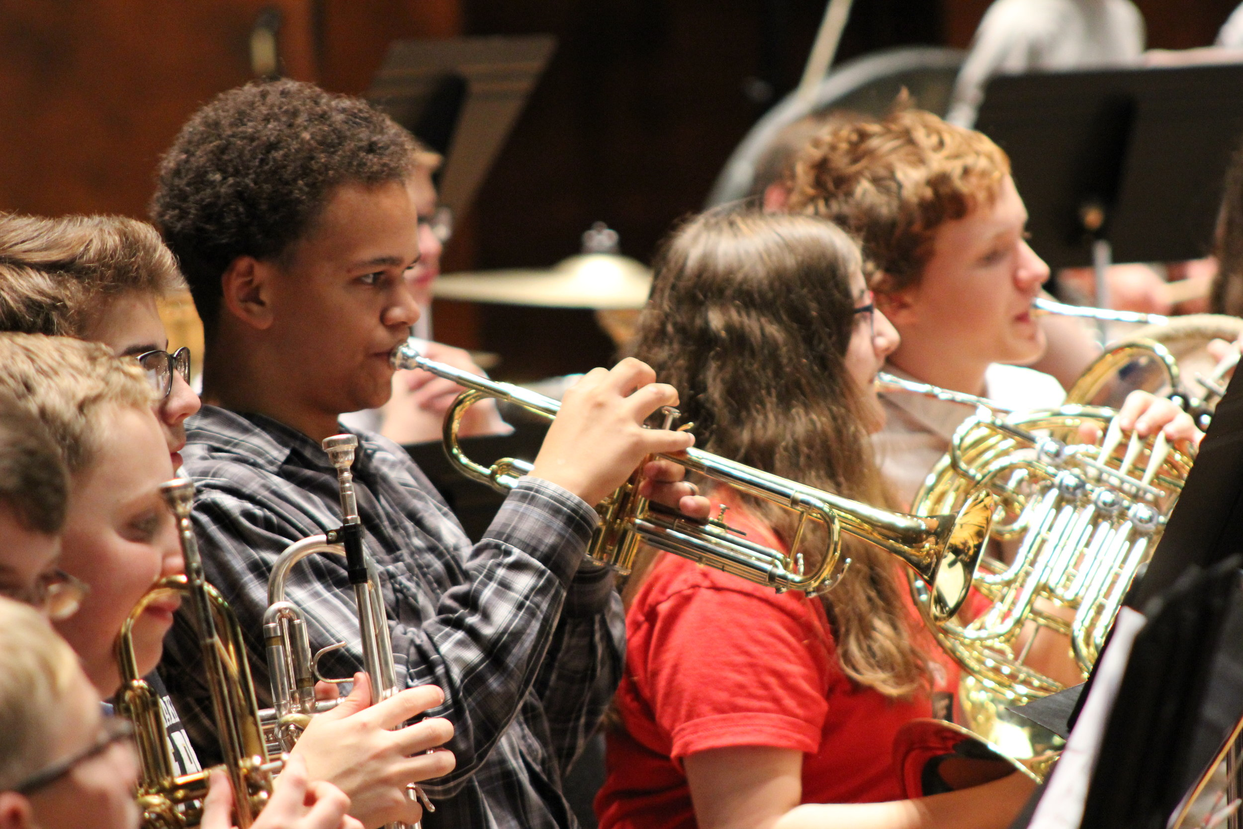 Junior High student playing the trumpet in rehearsal at a district festival