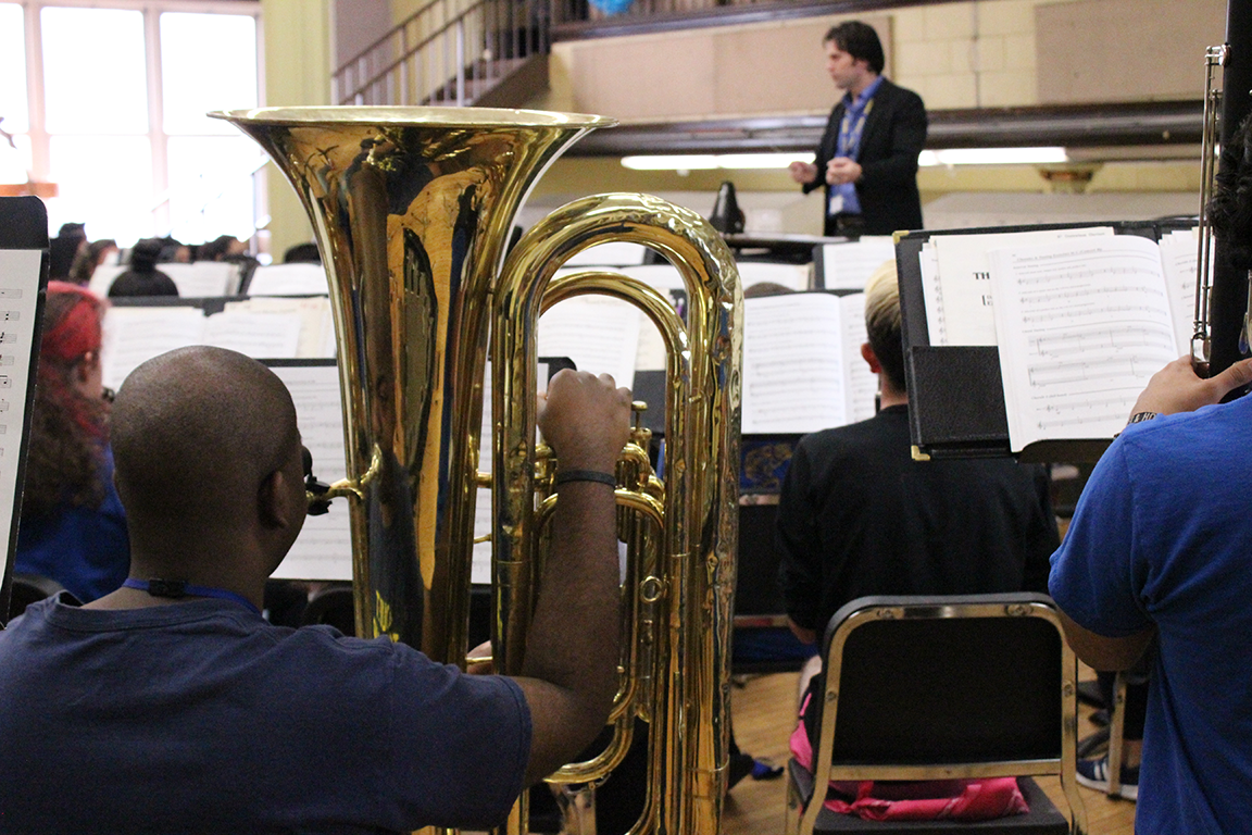 African-American student tuba player watches director during rehearsal at Joliet Central High School.