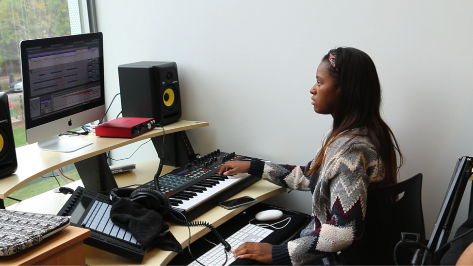 Female student working at digital music station with keyboard and computer
