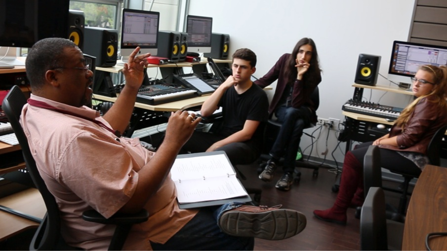 The author sitting with students discussing ongoing music technology projects